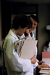 NHS 1980s doctor Dr Maura Stafford  tired antenatal unit clinic with consultant Mr Bamford, 5.30 pm. She has been working for over 24hrs without a break. Royal United Bath Hospital Somerset. 1989.