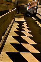 The setting sun casts an interesting checker-board pattern on a staircase.