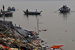 Unburnt body parts and  left overs after a hindu funeral are thrown in the river Ganga and thought to be very auspicious by the Hindus. Varanasi, Uttar Pradesh, India.