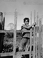 Ein kleiner Junge an einem Zaun in Copan, Honduras 1970er Jahre. A little boy on a fence at Copan, Hodnuras 1970s.