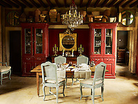The dining area's 19th century chandelier is a family heirloom and the room is furnished with Regency chairs and a Venetian cabinet
