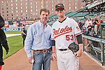 2011 Kentucky Derby winning trainer H. Graham Motion throws out the first pitch at Camden Yards in Baltimore to Baltimore Orioles pitcher Zach Britton.
