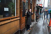 Man smoking and using a mobile phone outside a pub, Soho, London.