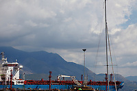 Gaeta: An impressive blue and red boat that is anchored in the port, against the background of the mountains that close the South side of the gulf and that make part of the Natural Park of Monti Aurunci. The view appears still more majestic because of the cloudy day. This is an enlargement of a part of the original photo.<br /> <br /> You can download this file for (E&PU) only, but you can find in the collection the same one available instead for (Adv).