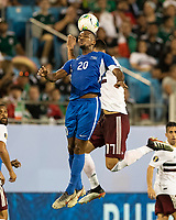 CHARLOTTE, NC - JUNE 23: Stephane Abaul #20 and Cesar Montes #17 contest a header during a game between Mexico and Martinique at Bank of America Stadium on June 23, 2019 in Charlotte, North Carolina.