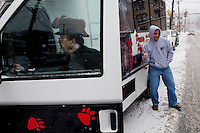 Inner Circle member Butch (last name) gets in the Punxsutawney Phil tour bus while (name) from Outer Banks, N.C., poses in front of the van for a photograph on Saturday, January 25.
