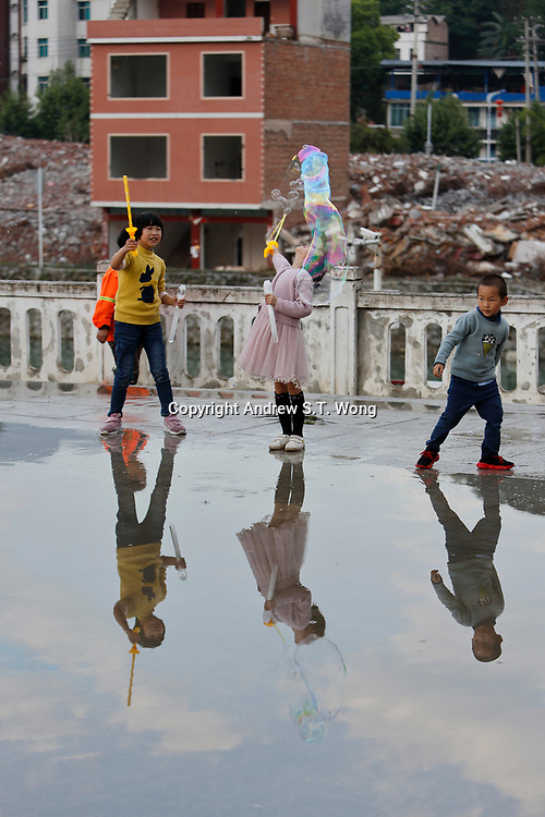 Children of the ethnic Bouyei Tribe play in front of a demolished old residential area at Wangmo County in China's southwestern Guizhou Province, April 2019.