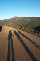 three long shadows on the walking path up to Las Medulas viewpoint spain castile and leon