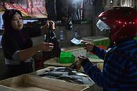 Bali, Indonesia.  Vendor Selling a Bag of Fish, Jimbaran Fish Market.