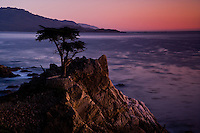A fine art landscape image of the Pacific Ocean along the California coast, after sunset, with a rosy hue along the horizon, reflecting onto the Pacific ocean as a creamy mauve color, with fading sunset light touching the western side of a rock outcropping.
