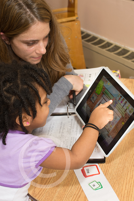 Education preschool 3-4 year olds SEIT working with girl in classroom using iPad or tablet computer