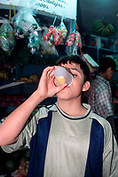 young man drinks a cup of sea turtle egg ( from olive ridley sea turtle, Lepidochelys olivacea ) in salsa from Ostional for legal sale in market, San Jose, Costa Rica, Pacific Ocean