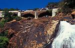 Train crossing the bridge over the Dudhsagar (sea of milk) waterfalls in Goa in India.