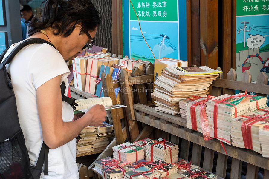 Yangzhou, Jiangsu, China.  Customer Examining Books at a Used Book Stand, Dong Guan Street.