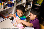 Preschool Headstart 3-5 year olds two boys eating breakfast cereal and milk one boy pouring milk for the other horizontal