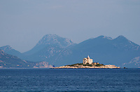 A lighthouse light house on an island outside the village, blue mountains in the background. Orebic town, holiday resort on the south coast of the Peljesac peninsula. Orebic town. Peljesac peninsula. Dalmatian Coast, Croatia, Europe.