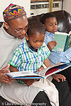 father at home reading picture book to 3 year old son with 8 year old son reading to himself in the background vertical