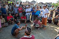 Bali, Indonesia.  Cock Fighting in an Indonesian Village.  Calling for Bets before the Match Begins.