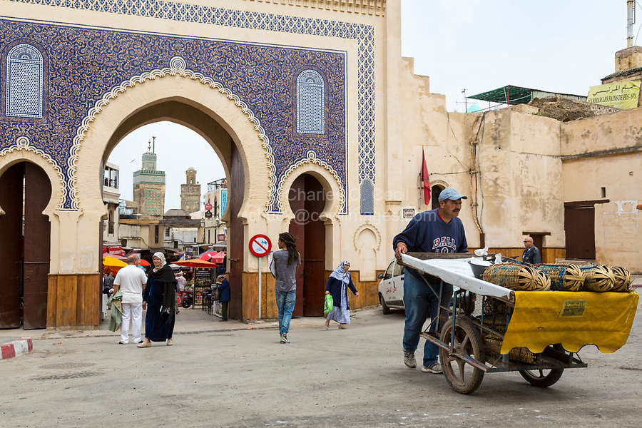 Fes, Morocco.  Fruit Vendor Pushing his Cart of Berries through the Bab Boujeloud, Entrance to Fes El-Bali, the Old City.  The minaret of the Bou Inania medersa is in the background.