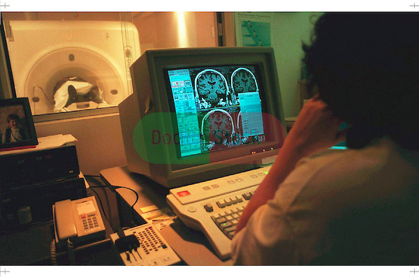 NOT MODEL RELEASED; FOR EDITORIAL USE ONLY... MRI technologist at computer monitoring a patient scan