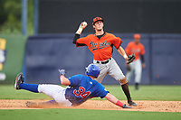 Carter Keiboom (10) of Walton High School in Marietta, Georgia playing for the Baltimore Orioles scout team throws to first base as TJ Collett (34) slides into second base during the East Coast Pro Showcase on July 28, 2015 at George M. Steinbrenner Field in Tampa, Florida.  (Mike Janes/Four Seam Images)