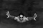 Underwater young male adult wearing white shirt, blue jeans and sunglasses swimming, Andrew Weingart Model, Model released; 609-760-9872; Underwater pool shoot