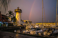 Fine Art Landscape Print Photograph in Puerto Vallarta Mexico of a rainbow over the yachts in the local marina. The Iconic Light-tower frames the background of this scene.