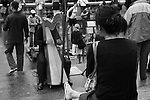 A harp player and his audience in Montmartre district. Paris, France. July 29, 2007.