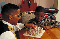 African-American father and son playing chess at home. Newark, New Jersey.