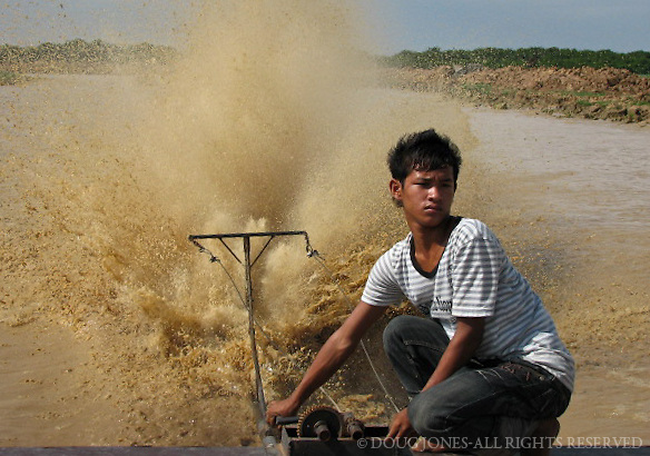 A young boy navigates a tourist boat through mud flats to the deeper waters of Tonle Sap Lake in Cambodia.