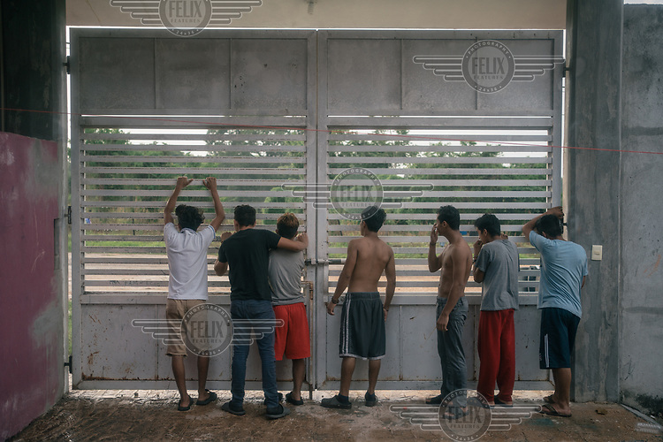 A group of unaccompanied Central American migrants, look out through a security gate in the unaccompanied minors section peeking outside at the La 72 shelter.