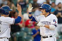 Round Rock Express outfielder Jim Adduci (24) is greeted at home after hitting a home run against the Oklahoma City RedHawks during the Pacific Coast League baseball game on August 25, 2013 at the Dell Diamond in Round Rock, Texas. Round Rock defeated Oklahoma City 9-2. (Andrew Woolley/Four Seam Images)
