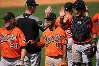 Baltimore Orioles second baseman Darell Hernaiz (80) and catcher Christopher Burgess (51) high fives teammates after a Minor League Spring Training game against the Detroit Tigers on April 14, 2021 at TigerTown in Lakeland, Florida.  (Mike Janes/Four Seam Images)