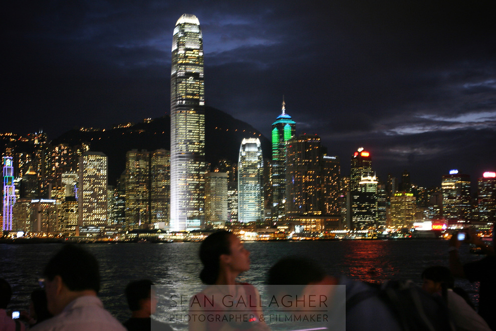 CHINA. Hong Kong. Tourists in front of the famous Hong Kong skyline. Officially the Hong Kong Special Administrative Region, it is a territory located on China's south coast on the Pearl River Delta. It has a population of 6.9 million people, and is one of the most densely populated areas in the world. 2008
