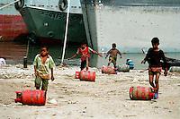 Children unloading gas bottles from a ship.