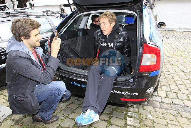 Daniel Benson Managing Editor of Cycling News interviews Daniel Martin (IRL) Garmin-Barracuda as he waits in the boot of the team car before the team presentations at the Palais Provincial in Liege city centre before the 98th edition of Liege-Bastogne-Liege 2012. 21st April 2012.  <br /> (Photo by Eoin Clarke/NEWSFILE).
