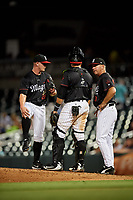 Birmingham Barons pitching coach Richard Dotson (38) talks with catcher Alfredo Gonzalez (1) and relief pitcher Matt Foster (20) in a mound visit during a game against the Tennessee Smokies on August 16, 2018 at Regions FIeld in Birmingham, Alabama.  Tennessee defeated Birmingham 11-1.  (Mike Janes/Four Seam Images)
