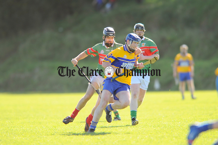 Stiofan Fitzpatrick of Sixmilebridge is tackled by Clooney-Quin's  Ger Leamy during their Intermmediate semi final at Tulla. Photograph by John Kelly.