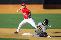 Josh Gardiner (10) of the Radford Highlanders turns a double play as Sean Ullrich (28) of the Missouri Tigers slides into second base at Wake Forest Baseball Park on February 21, 2014 in Winston-Salem, North Carolina.  The Tigers defeated the Highlanders 15-3.  (Brian Westerholt/Four Seam Images)