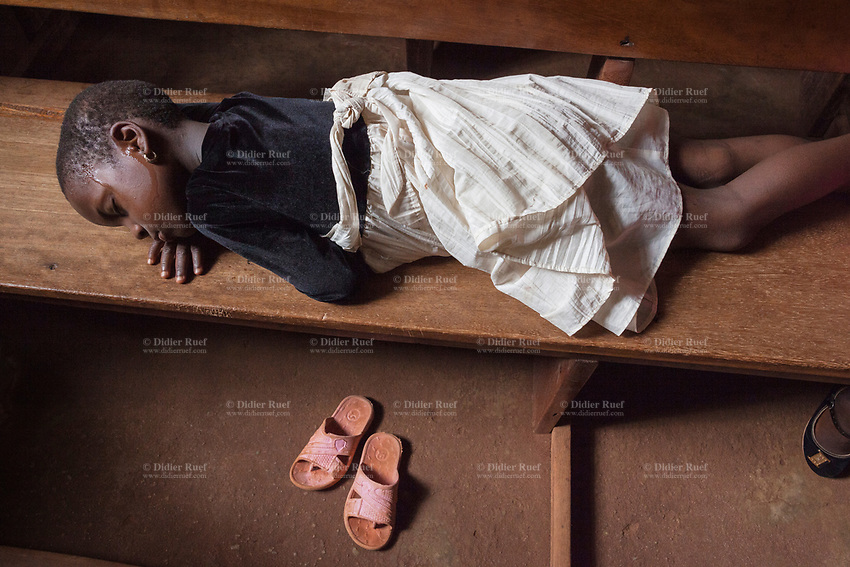 Nigeria. Enugu State. Awhun. Saint Luke's Catholic Parish.  A sweating young girl fell asleep on a wooden bench during an Igbo religious wedding ceremony. Plastic sandals on the ground. 29.06.19 © 2019 Didier Ruef