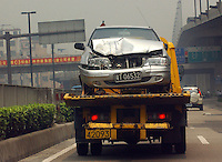 A smashed car is transported along a highway near Guangzhou, China.  China has the highest car accident rate in the world with large numbers of inexperienced drivers taking to the road daily..