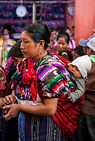 Chichicastenango, Guatemala.  Quiche (Kiche, K'iche') Woman with Baby on Back in Indoor Market, Sunday Morning.