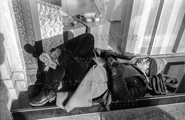 Milano, piazza Missori, zona centro. Un uomo dorme davanti a un negozio con dei pacchi regalo in vetrina --- Milan, Missori square, downtown. A man sleeping in front of a shop with gift packages displayed in the window