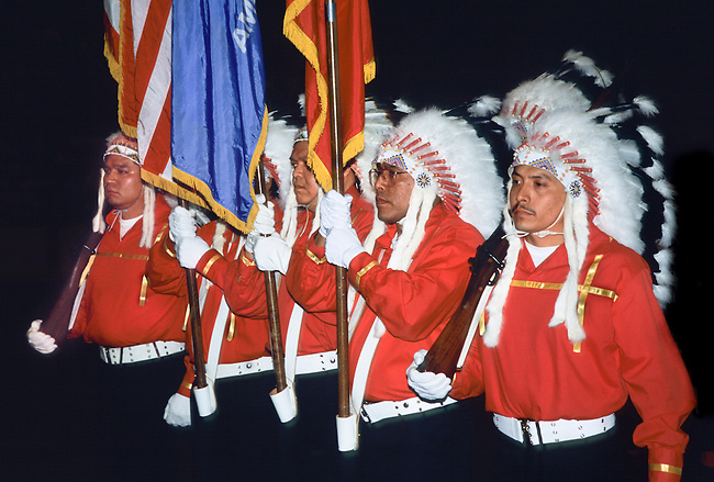 Armed color guards dressed in traditional feather headdresses carry in the flags during Grand Entry at the Red Earth Indian Festival and Pow Wow, Oklahoma City OK.