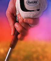 Detail of gloved hands in a grip with a club against a digitally enhanced backgound.