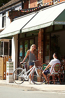 Zoe talking to Sam outside cafe , holding white Charge Decanter bicycle .   Sunninghill, Berks.    July   2013.      pic copyright Steve Behr / Stockfile