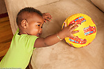 12 month old baby boy cruising reaching desired toy ball on couch