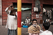A man combs his hair while the other one gets a shave on the streets of Kolkata in West Bengal, India.