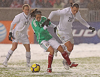 USA's Abby Wambach (R) has the ball taken from her by Mexico's Lupita Worbis (C) as Kristine Lilly looks on at Rio Tinto Stadium March 31, 2010 in Salt Lake City, Utah. The USA women won the match over Mexico 1-0.