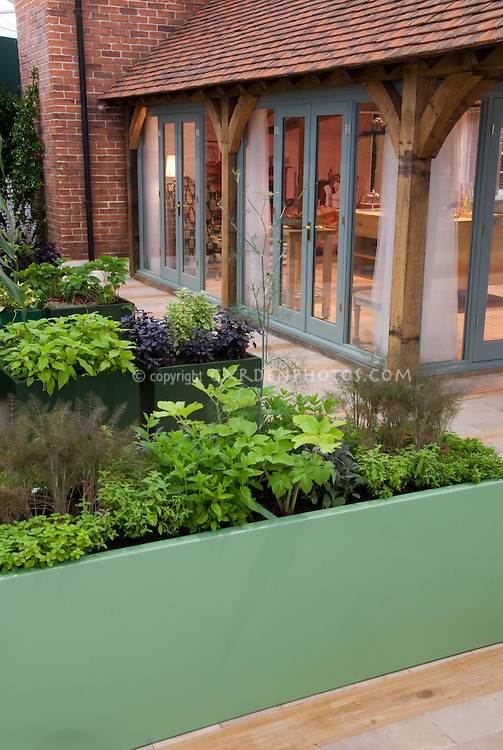 Raised bed vegetable garden with herbs, and upscale house near to kitchen doors